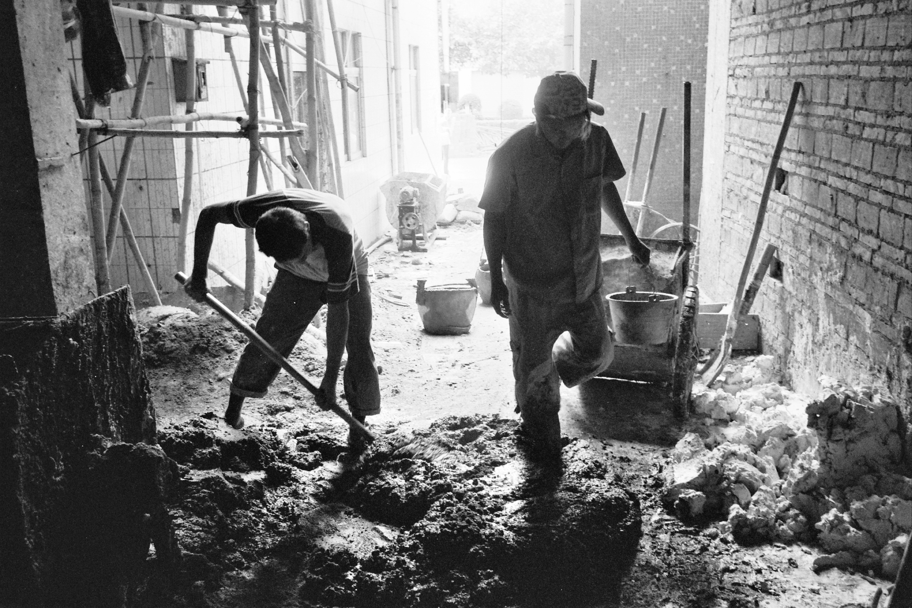 Construction workers mix concrete for a new apartment building downtown (Dongguan, China)